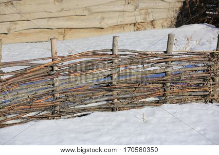 abstract wooden wattle fence in winter day