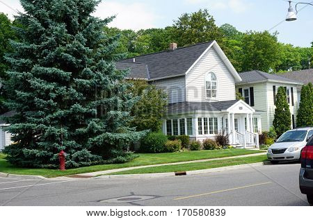 HARBOR SPRINGS, MICHIGAN / UNITED STATES - AUGUST 4, 2016: A home beside a large blue spruce tree (Picea pungens) at the corner of Church and West Third Streets in Harbor Springs.