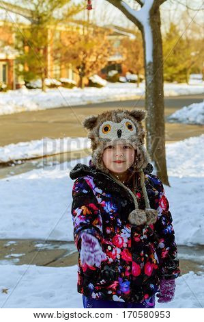 cute little girl is going skate outdoors Winter snow little girl playing with snow