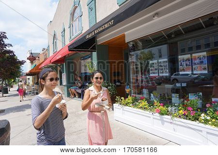 HARBOR SPRINGS, MICHIGAN / UNITED STATES - AUGUST 4, 2016: A woman and a girl eat big bowls of Kilwin's ice cream while walking on Main Street in downtown Harbor Springs.