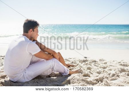 Cute couple sitting down on the beach