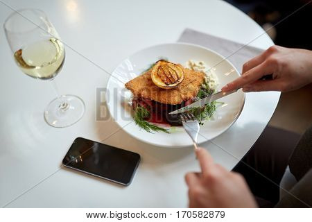food, new nordic cuisine and people concept - woman with smartphone eating breaded fish fillet with tartar sauce and oven-baked beetroot tomato salad with fork and knife at cafe or restaurant