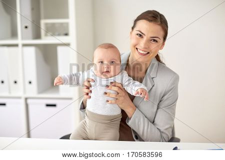 business, motherhood, multi-tasking, family and people concept - happy smiling businesswoman with baby at office