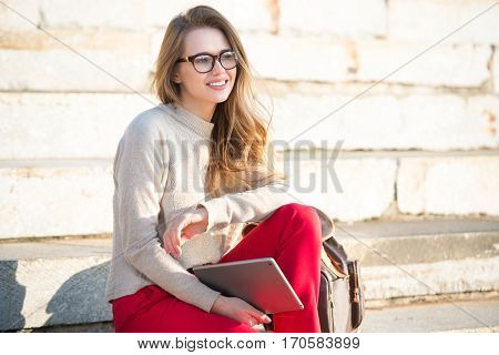 Happy beautiful student girl wearing eyeglasses sitting on college steps in the capus with a bag and tablet
