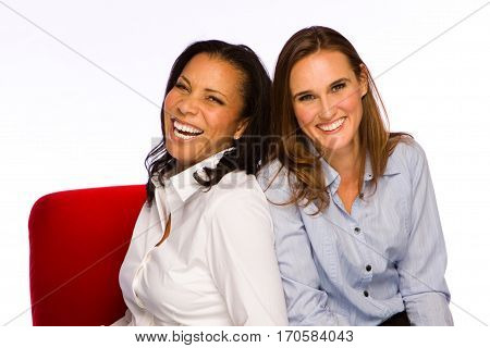 Friends laughing and talking sitting in a red chair.