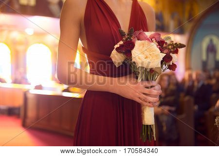 Wedding ceremony day. bridesmaid girl wearing elegant red dress holding flowers bouquet at Wedding ceremony in catholic church.