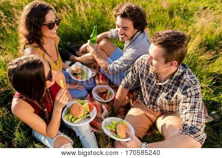 Friends sitting in grass and having sandwiches at BBQ party in meadow
