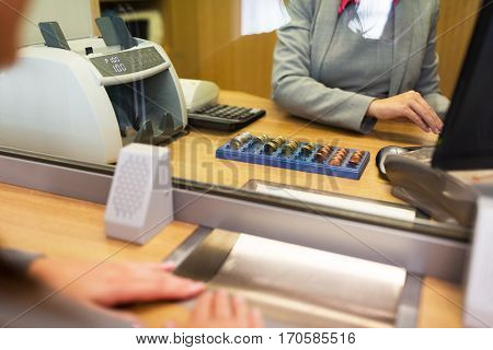 people, money, saving and finance concept - clerk counting coins for customer at bank office or currency exchanger