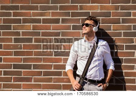 style, music, technology and people concept - happy smiling young man in headphones and sunglasses with bag over brickwall