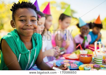 Close up of cute boy smiling in front of other children during a birthday party on a park