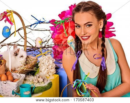 Easter girl holding bunny and eggs. Holiday style holding and group of rabbits in basket with flowers. Isolated. Young woman with present box at home. White background.