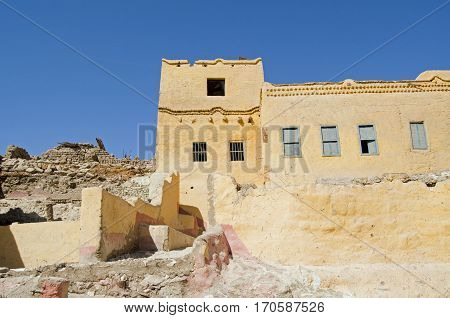 A traditional mud brick home painted yellow with some elegant detail in the village of Qurnet Murai. The house is one of many built over the top of Ancient Egyptian tombs on the West Bank of the Nile in Luxor Egypt.