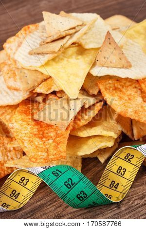 Centimeter With Heap Of Salted Crisps And Cookies, Concept Of Unhealthy Food And Slimming