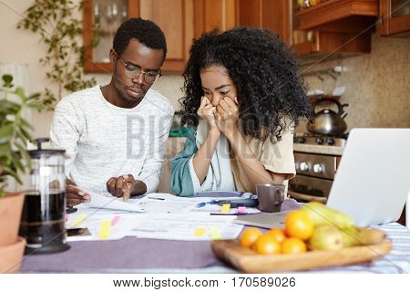 Stressed Young African Wife Holding Hands On Her Face, Listening In Desperation To Her Husband Readi