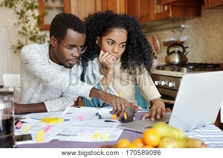 African Family Of Two Sitting At Table In Their Kitchen And Paying Bills Online Using Laptop Compute