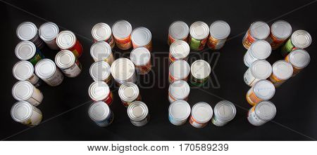 Canned goods placed on black background spelling out