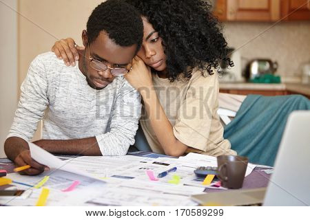 Unhappy Young African Couple Facing Financial Stress: Black Man In Spectacles Holding Notification I