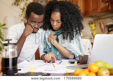 Financial Problem And Economic Crisis. Young Dark-skinned Couple Managing Finances, Sitting At Kitch