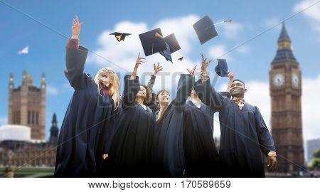 education, graduation and people concept - group of happy international students in bachelor gowns throwing mortarboards up over london background