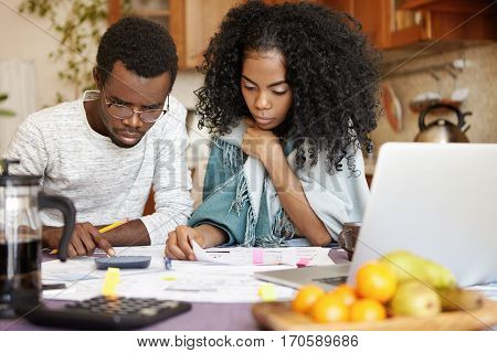 Stressed African Couple Doing Paperwork In Kitchen: Serious Female Reading Document, Her Husband Mak