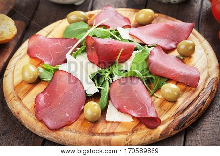 Charcuterie board with italian bresaola cured beef meat slices, cheese and rocket salad