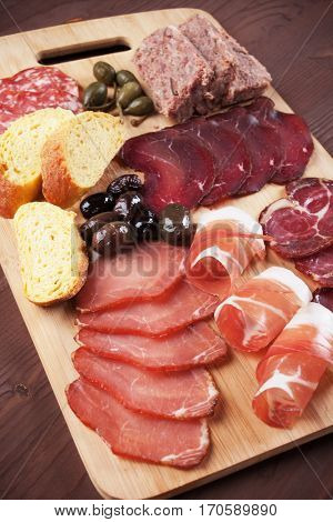 Charcuterie board with cured meat, olives and bread