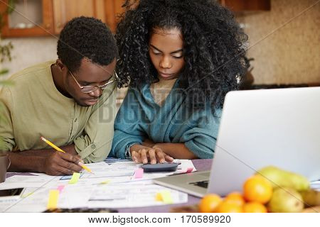 Unhappy African Family Facing Financial Stress, Having Big Trouble While Calculating Domestic Budget