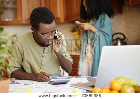 Young African Husband Making Notes With Pencil, Talking On Mobile Phone With Utility Service, Beggin