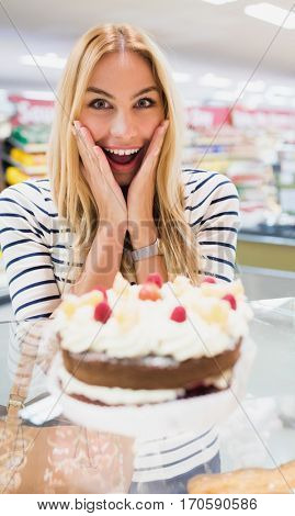 Happy woman with mouth open in front of cake qt grocery store