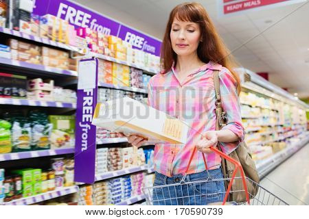 Portrait of woman putting product in shopping basket at supermarket