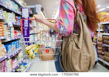 Close up view of woman doing grocery shopping with shopping basket at supermarket