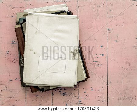 stack of retro folders on old pink wooden background