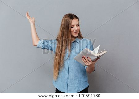 Smiling Woman in shirt rehearses in studio with book in hand. Isolated gray background
