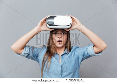 Surprised Woman in shirt take off virtual reality device and looking at camera. Isolated gray background