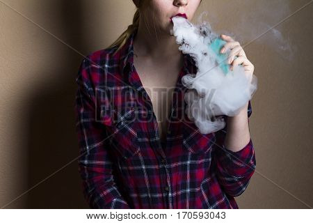 vape (e-cigarette electronic cigarette) girl with red lips in red shirt smoking