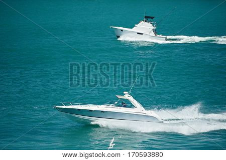 Private fishing boats moving in blue water. Two motor boats at sea