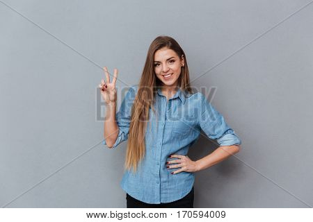 Woman in shirt showing peace sign with arm at hip and looking at camera. Isolated gray background