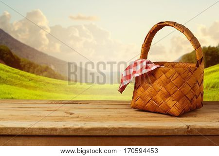 Picnic basket with checked tablecloth on wooden table over beautiful landscape background