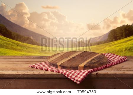 Wooden cutting board with checked tablecloth on table over beautiful landscape background