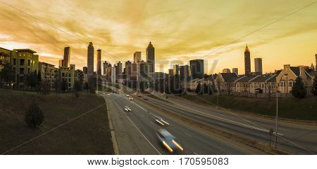 Panoramic view of downtown Atlanta and highway leading to it at sunset.