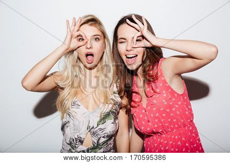 Portrait of two laughing female friends looking at camera through fingers isolated on a white background