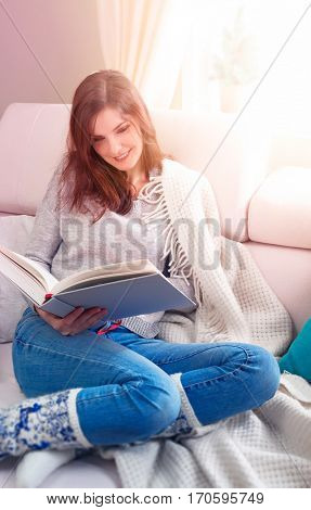 Beautiful girl reading book at soft white sofa with warm plaid. Sunny interior of room bright sunlight glowing from window