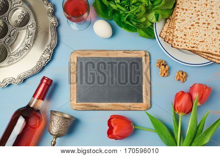 Passover holiday concept with chalkboard seder plate and matzoh on wooden background. Top view from above