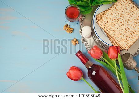 Passover holiday concept seder plate matzoh and tulip flowers on wooden background. Top view from above
