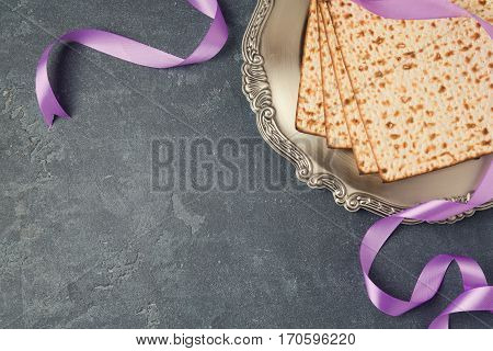 Passover holiday concept with seder plate and matzoh on dark background. Top view from above