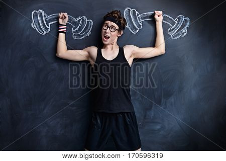 Funny weak guy raises heavy dumbbells, drawn on a blackboard. Sports and health concept.