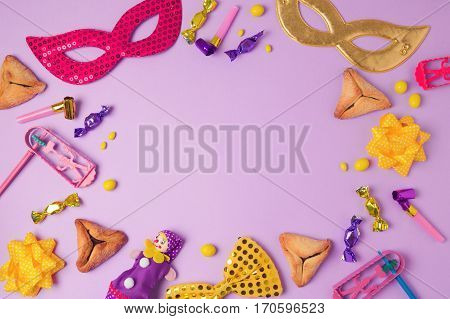 Purim holiday concept with carnival mask hamans ears cookies and party supplies on purple background. Top view from above with copy space