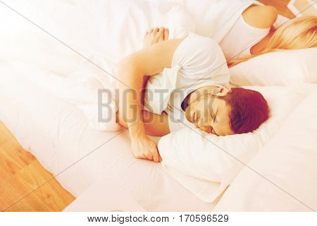 people, relationship difficulties, conflict and family concept - couple sleeping back to back in bed at home