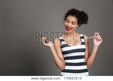 Portrait of young african american woman listening to music with earphones over gray background