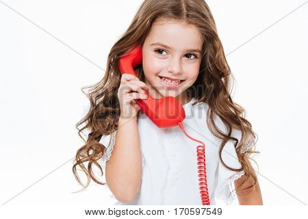 Cheerful cute little girl talking on red telephone over white background